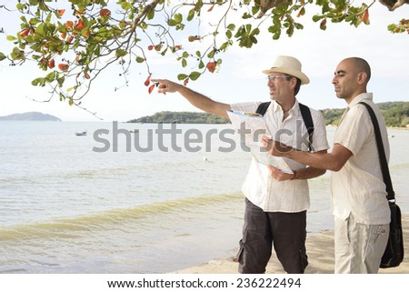 Sightseeing: Gay couple on vacation pointing at destination - stock photo