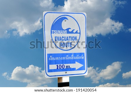 Sign an evacuation route at danger of a tsunami on a blue sky background.