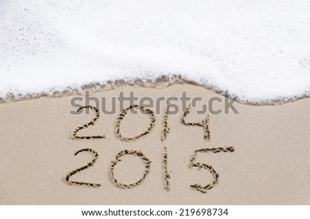 "Sign ""2014 and 2015"" on the sandy beach by ocean"