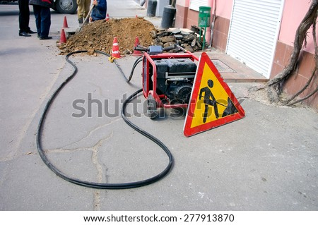 Sign and portable generator on road construction work in the city - stock photo