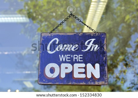 sign at a shop with the text: come in we're open - stock photo
