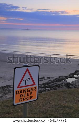 sign at cliff edge near beach at sunset - stock photo