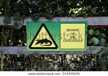 Sign attached to a wooden fence warning people to beware of the crocodiles