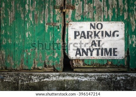 Sign attached to the old green wooden gates of a barrack stating that parking is not allowed at anytime - stock photo