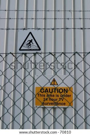 Sign, Caution - 24hr Surveillance (selective focus to distant) - stock photo