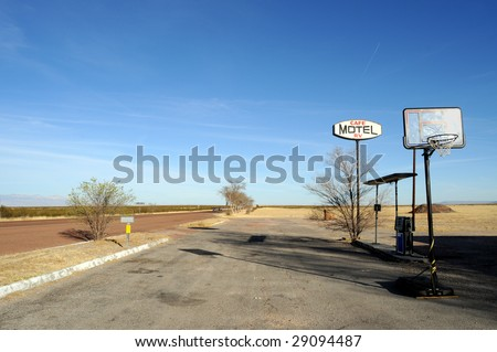 Sign for an abandoned motel on a desert road in rural Texas, with basketball court - stock photo