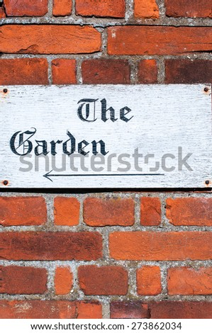 Sign for 'The Garden' on a brick wall - stock photo