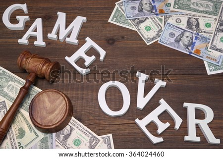 Sign Game Over, American Dollars Cash  Judges Gavel On The Wood Rough Table Background. Concept For  Bankruptcy, Gambling, Fraud, Bribe, Bail, Illegal Income, Tax. Overhead View - stock photo