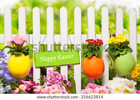 Sign Happy Easter hangs on the garden fence - stock photo
