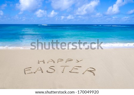 "Sign ""Happy Easter"" on the sandy beach by the ocean - stock photo"