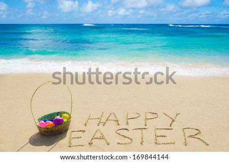 "Sign ""Happy Easter"" with basket and eggs on the sandy beach by the ocean - stock photo"