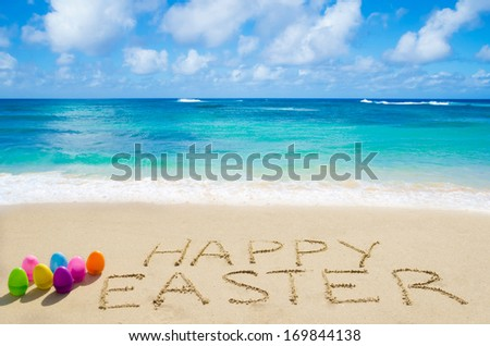 "Sign ""Happy Easter"" with color eggs on the on the sandy beach by the ocean - stock photo"