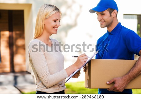 Sign here please! Smiling young delivery man holding a cardboard box while beautiful young woman putting signature in clipboard  - stock photo