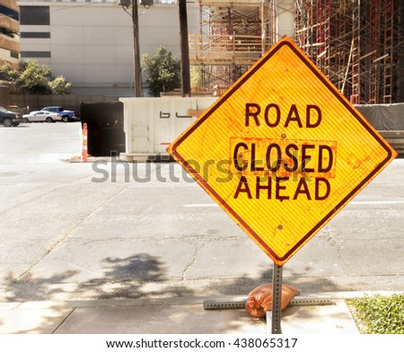 Sign in a construction area warning that the road ahead is closed.