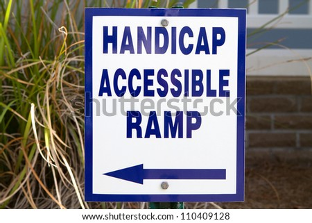 Sign in front of a  building points to a handicapped accessible ramp for use by the disabled. - stock photo
