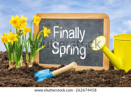 Sign in the flower bed with the text Finally Spring - stock photo
