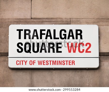 Sign indicating to the public they are in Trafalgar Square, best known for Nelson's Column, a huge monument towering the area at 169 feet and 3 inches, it's a tourist favorite and cultural hotspot. - stock photo