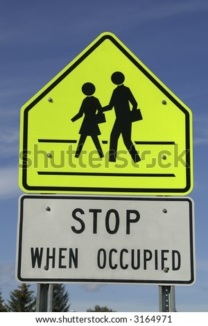 Sign near school to tell motorists to stop when the crosswalk is occupied - stock photo