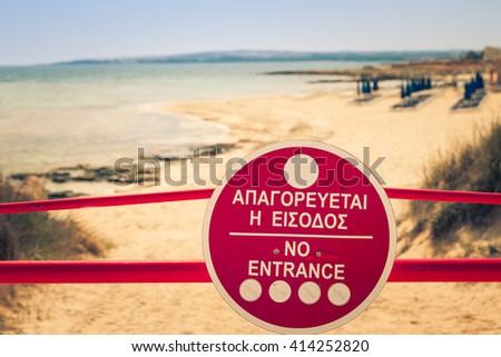 Sign No Entrance before the beach near of Ayia Napa and Cavo Greco, Cyprus island, Mediterranean Sea. Retro film simulation. - stock photo