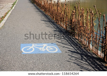sign of a bike road close to a lake