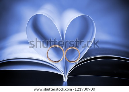 sign of a heart and beautiful wedding golden rings - stock photo