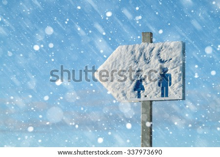 Sign of the toilet in the street, covered with snow,  blizzard. The plate removed close-up, is led snowfall. The inscription WC can be seen under the snow. Copy space. - stock photo