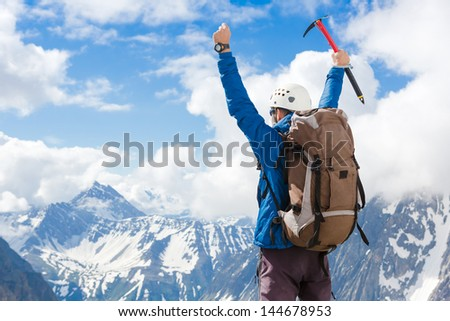 Sign of victory: climber on the top of the mountain