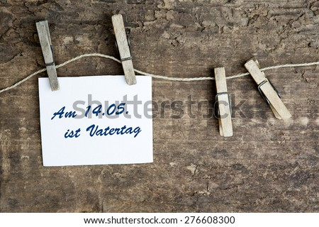 sign on a clothes line with german text:Am 14.05. ist Vatertag (fathers day is on 14.05.) - stock photo