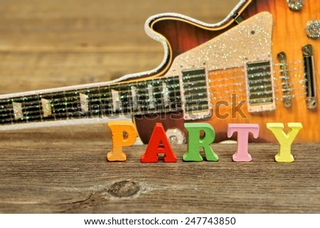 Sign PARTY made from wooden Letters on Timber Board and Electric Guitar Silhouette on the Background - stock photo