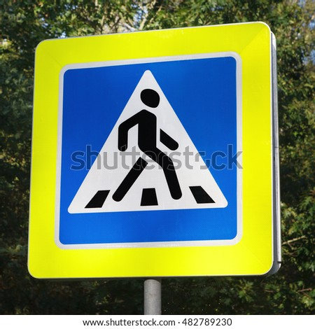 sign pedestrian crossing on background of green trees