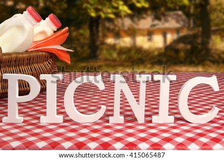 Sign Picnic Made From White Letters On The Table With Basket And Red Tablecloth Near Country House At Summertime