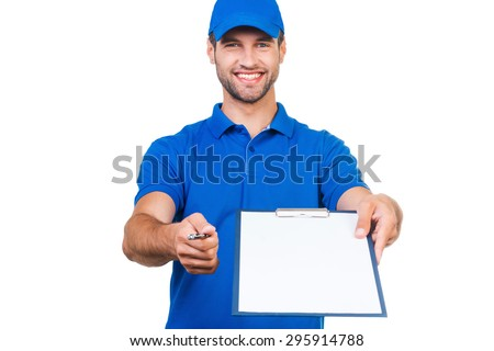 Sign please! Smiling young courier stretching out clipboard and pen for signing while standing against white background - stock photo