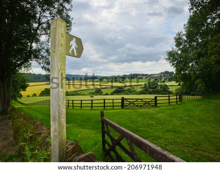 Sign post indicating a public footpath through British countryside - stock photo