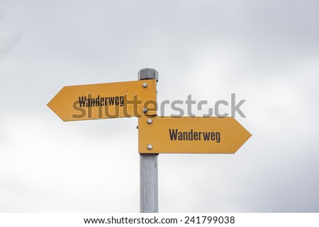 Sign post of swiss alps indicating the hiking trails (Wanderweg) - stock photo
