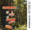 Sign post on bush track giving directions to New Zealand towns and cities. - stock photo