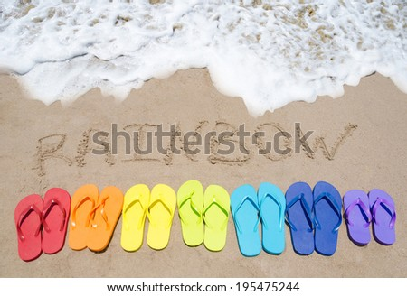 """Sign """"Rainbow"""" and color flip flops on sandy beach by the ocean in sunny day - stock photo"""