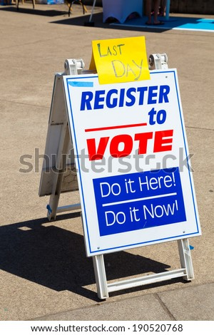 Sign reading Last Day Register to Vote trying to get voters to signup for political voting registration. - stock photo