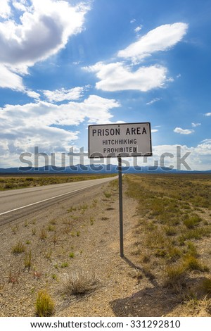"Sign reading ""Prison area, hitchhiking prohibited"" stands in front of a prison/penitentiary in the desert landscape beneath a cloud filled blue sky. Taken in the Utah state. Retro style image"
