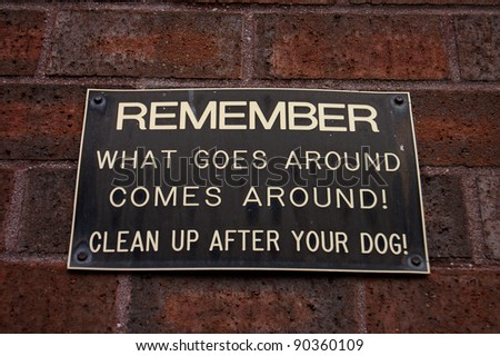 Sign reads: REMEMBER WHAT GOES AROUND COMES AROUND! CLEAN UP AFTER YOUR DOG!
