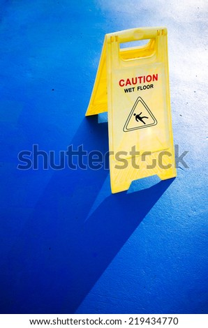 Sign showing warning of caution wet blue floor , close up shot of a yellow caution on blue floor - stock photo