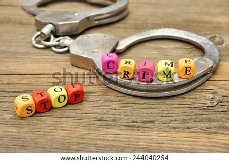 Sign Stop Crime and Handcuffs on Wooden Table - stock photo