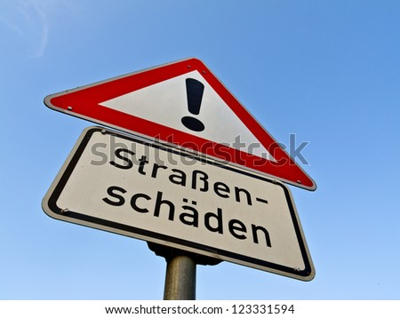 "Sign ""Strassensch�¤den"" (Road Damage) before blue sky"
