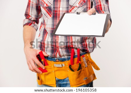 Sign this. Close-up of handyman with tool belt stretching out clipboard with paper standing against grey background - stock photo