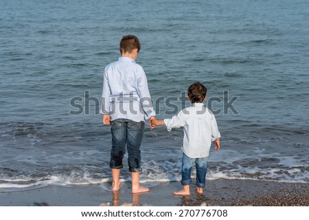 Sign up portrait of two children on beach - stock photo