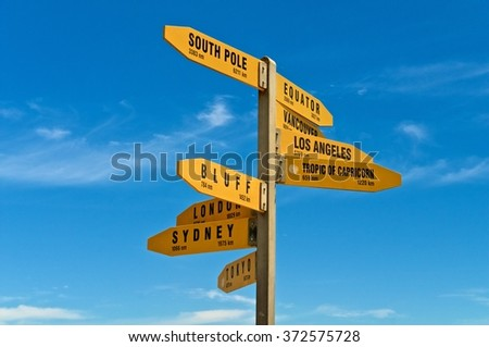 Sign with distances in km and nm from Cape Reinga, New Zealand. - stock photo