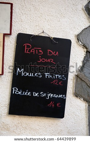 Sign with French text: dish of the day ,moules frites 12 euro and poulee de St. Jacques 14 euro