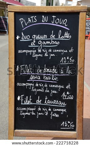 Sign with French text: dishes of the day starting at 12,50 euro - stock photo