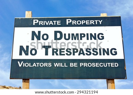 Sign with no dumping and no trespassing on it. - stock photo