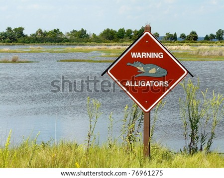 Sign with spikes in St. Marks National Wildlife Refuge, Florida, warning of alligators in the swampy & marshy areas.