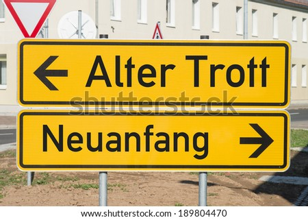 Sign with the german words Old routine and a new beginning / German sign - stock photo